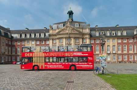 Bus with tourists in front of the Schloss (castle) in Munster, Germany. Former residence for the prince-bishops, now it is the administrative centre of the University of Munster.