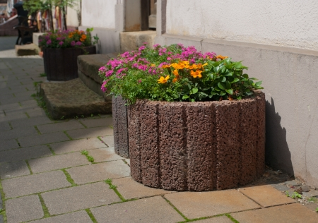 planters: large stone planters with blooming flowers on a sidewalk
