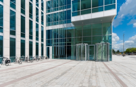 entrance of a modern office building with revolving doors