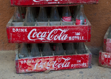 coke bottle: Vintage Coca-Cola crates with empty bottles. Coca-Cola was invented in the late 19th century by John Pemberton and is sold in over 200 countries.