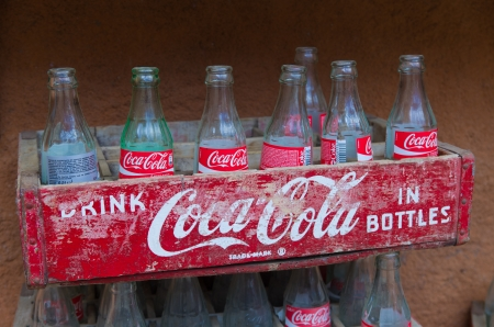 coke bottle: Vintage Coca-Cola crate with empty bottles. Coca-Cola was invented in the late 19th century by John Pemberton and is sold in over 200 countries. Editorial