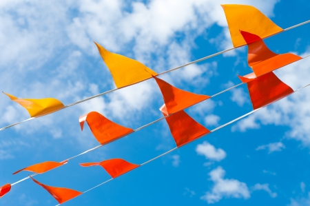 red and orange bunting flags against a blue sky photo