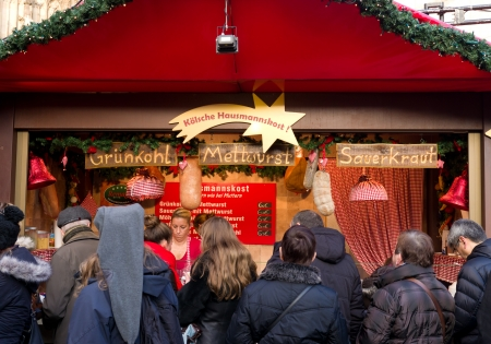 weihnachtsmarkt: People in front of a food stand at the christmas market in Cologne, Germany. Its one of the largest in the country with 7 separate markets all in the city center