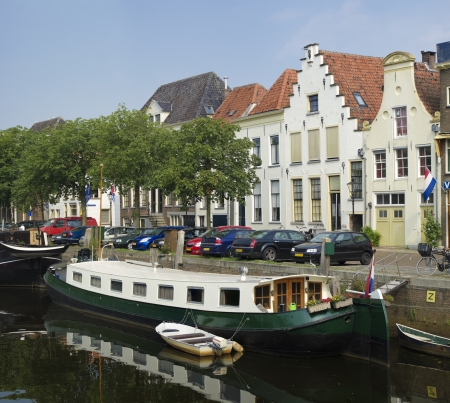 monumental: canal in zwolle, netherlands with floating houseboat and monumental houses