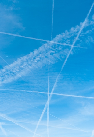 lots of contrails in a blue sky made by airplanes