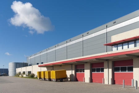large warehouse with red loading docks and several trailers for rent Editorial