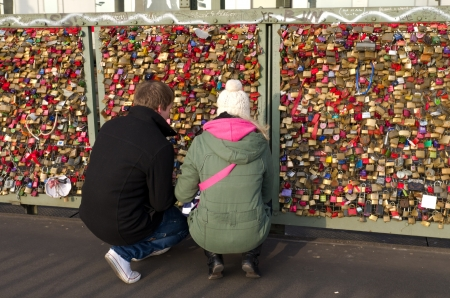 Young couple placing their 'love lock' at the Hohenzollern bridge in Cologne, Germany as a symbol for their love. Since 2008 people have placed love padlocks on the fence between the sidewalk and the tracks. Dutch band Nits dedicated a song to this in the