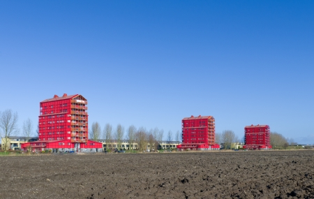 figuring: modern red apartments in Almere, Netherlands. They are called red thunders and figuring the transition from the outer residential areas to the agricultural polders