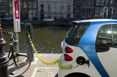 electric car plugged in next to an amsterdam canal