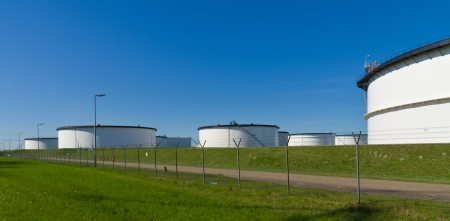 large white storage tanks for petrol and oil in the rotterdam harbor area photo
