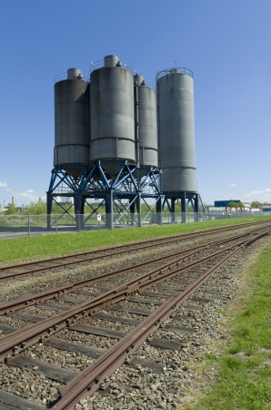 several industrial processing tanks for the chemical industry next to a railroad photo