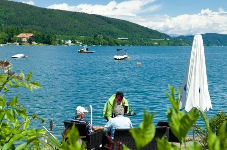 twee mannen worden geserveerd aan de rand van de Wörthersee in Velden, Oostenrijk Het meer strekt zich uit van de Karinthische hoofdstad Klagenfurt in het oosten naar Velden in het westen