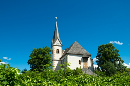 exterior of the church in Maria Worth, Austria. A first St. Marys Church was erected about 875 during the Christianization of Carinthia.  Todays parish church Saints Primus and Felician stands on the highest point of the peninsula, with the neighbouring