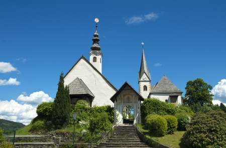 neighbouring: exterior of the church in Maria Worth, Austria. A first St. Marys Church was erected about 875 during the Christianization of Carinthia.  Todays parish church Saints Primus and Felician stands on the highest point of the peninsula, with the neighbouring