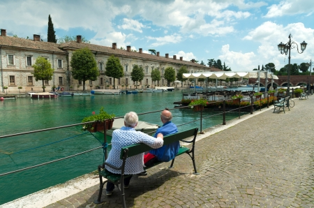 autochthonous: two elderly men enjoying the view in the picturesque harbor of peschiera del garda.