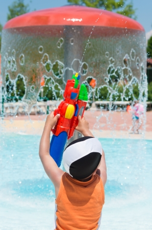 little boy having fun with his water gun in a swimming pool photo