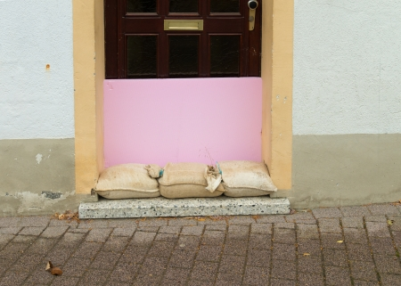 sandbags and wood plate in front of a door in case of a flooding photo