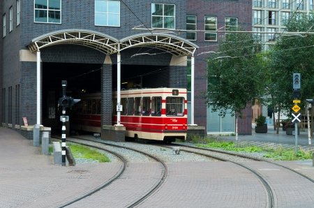 htm: red HTM tram entering a tunnel in den haag, netherlands. Since 2002 the HTM exploits the city network passenger transport