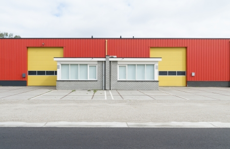 colorful industrial warehouse with yellow roller doors and small office part photo
