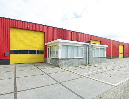 industrial warehouse with yellow roler doors and a small office part