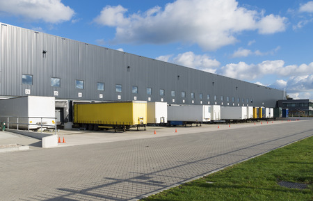 exterior of a large warehouse with loading docks and several trailers in front
