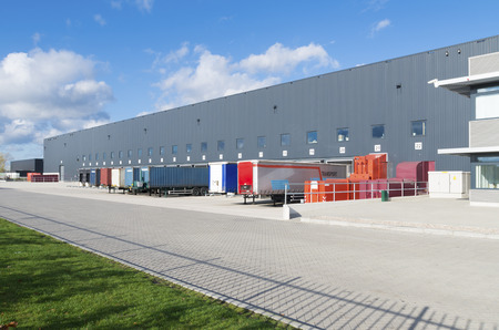 warehouse building: exterior of a large warehouse with loading docks and several trailers in front Editorial