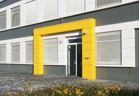 modern white office building with yellow entrance photo