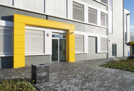 modern white office building with yellow entrance Banco de Imagens