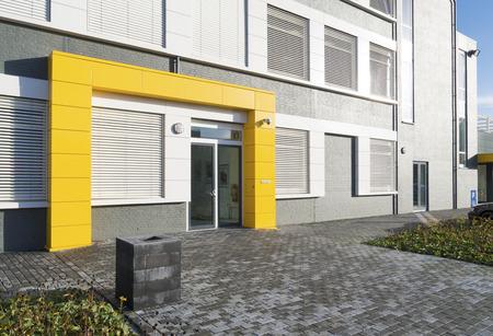 moderne witte kantoorgebouw met gele ingang