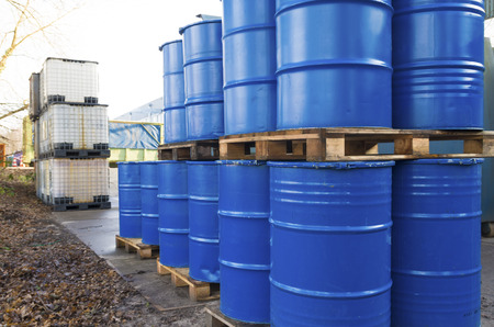 old container: piled up empty blue oil barrels Stock Photo