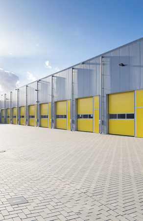 exterior of a commercial warehouse with yellow roller doors