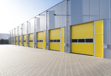 steel blue: exterior of a commercial warehouse with yellow roller doors