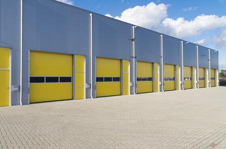 extérieur d'un entrepôt commercial avec des portes à rouleaux jaunes