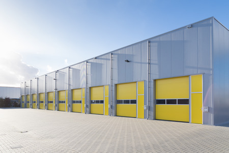 exterior of a commercial warehouse with yellow roller doors photo