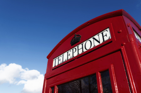 classic red uk telephone box against a blue sky photo
