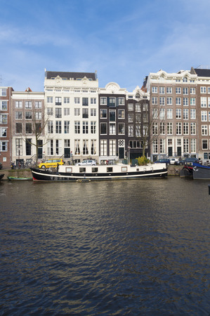 levied: amsterdam canal with historical houses. Most of them are very small, because in earlier ages the tax was levied on the basis of the width of the facade.