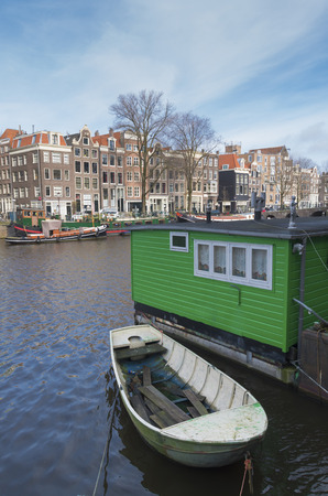 levied: amsterdam canal with houseboat and historical houses. Most of them are very small, because in earlier ages the tax was levied on the basis of the width of the facade.