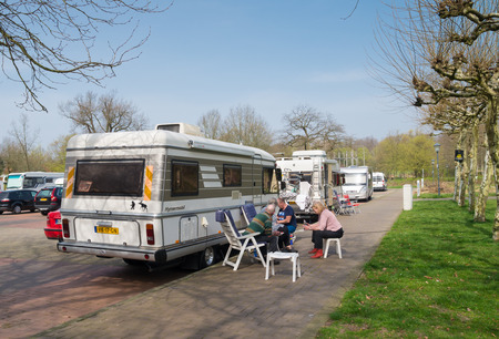 Dutch people next to their rv on a parking area. Mobilhomes are very popular among seniors, because they have money and time