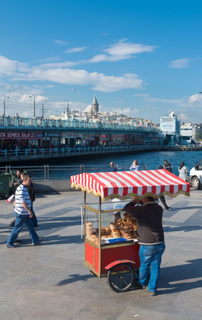 street vendor selling food in istanbul with the Galata bridge in the background. Eating on the street is part of local life here