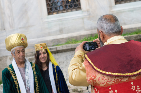traditional turkish man taking pics of some dressed tourists. Istanbul is one of the most important tourism spots not only in Turkey but also in the world.