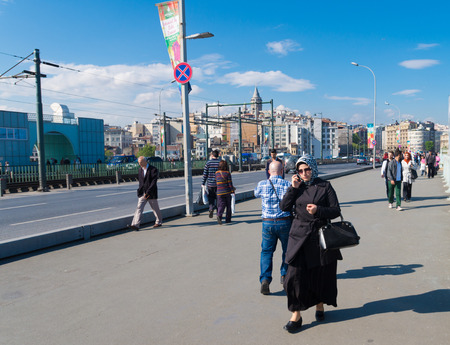 purdah: Muslim woman holding a cell phone on the Galata bridge in istanbul. In turkije 65% of the women are wearing some sort of head coverage outdoors