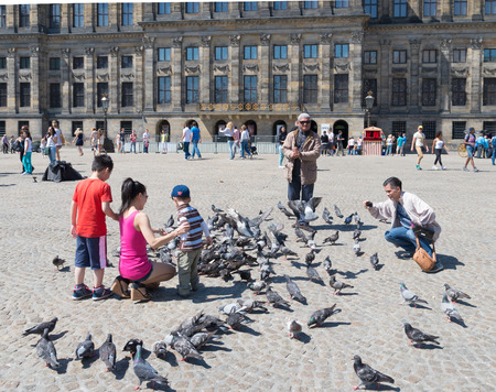 dam square: asian couple with kids feeding pigeons on the amsterdam Dam square. Editorial
