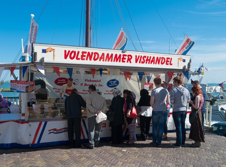 volendam: people in front of a fish stall in volendam, netherlands. This village is wellknown by tourists for its long forgotten costumes and fishing boats Editorial