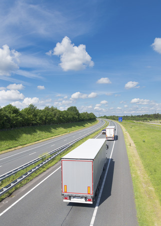 highway with two white trucks in the netherlands