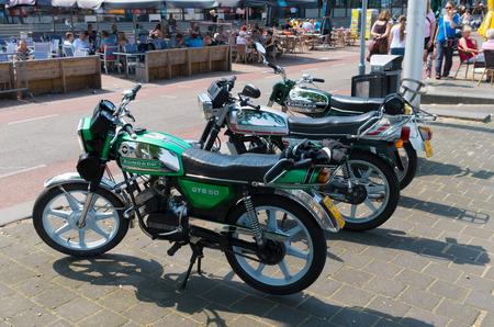 economic revival: oldtimer zundapp mopeds parked on a sidewalk in Nijmegen, netherlands. The name Zündapp is a contraction of the company name Zunder und Apparatenbau GmbH Nürnberg.