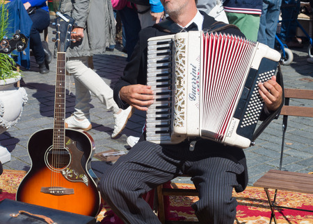 gitar: street artist playing his guerrini accordeon in the streets of zutphen, netherlands