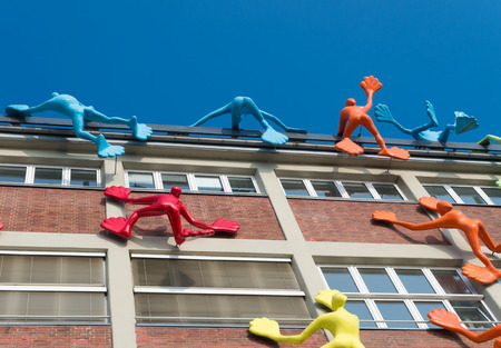 man made structure: colorful figures on an office building in dusseldorf, germany. This office building is emphasized by 28 giant plastic figures, known locally as Flossies, climbing the dockside of the office