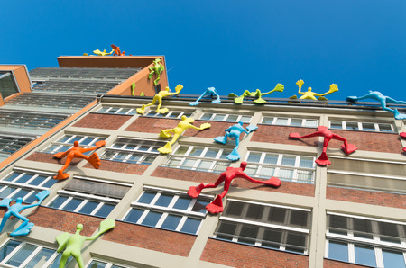 emphasized: colorful figures on an office building in dusseldorf, germany. This office building is emphasized by 28 giant plastic figures, known locally as Flossies, climbing the dockside of the office