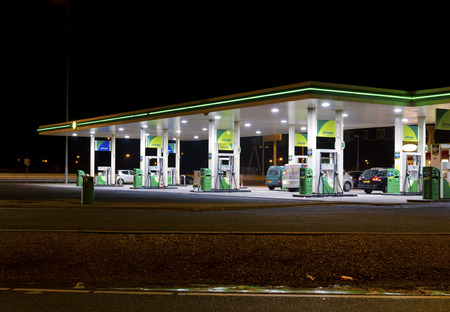 bp: BP gas station at night. BP is a petroleum company with its headquarters in London. The company operates in around 80 countries