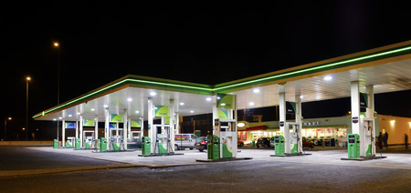 opec: BP gas station at night. BP is a petroleum company with its headquarters in London. The company operates in around 80 countries